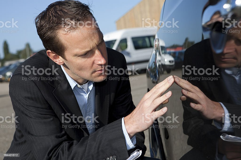 Close-up of accessor examining car damage for insurance stock photo