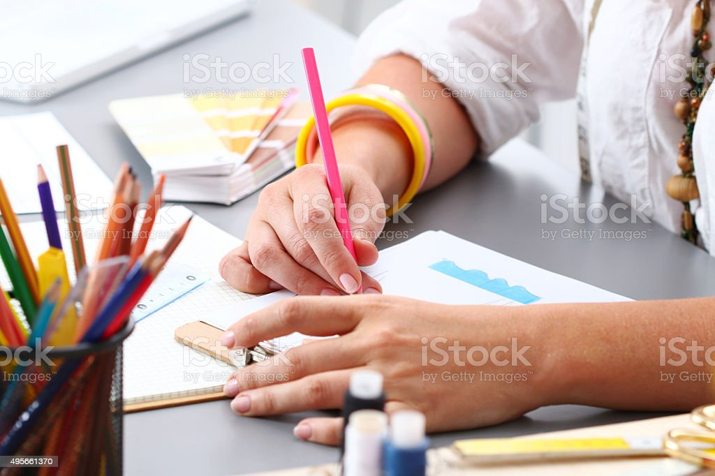 Close-up of adult female dressmaker drowing some clothing design stock photo