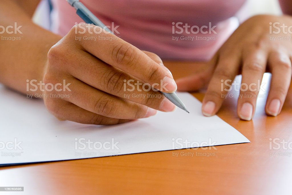 Close-up of adult hands writing with pen and paper stock photo
