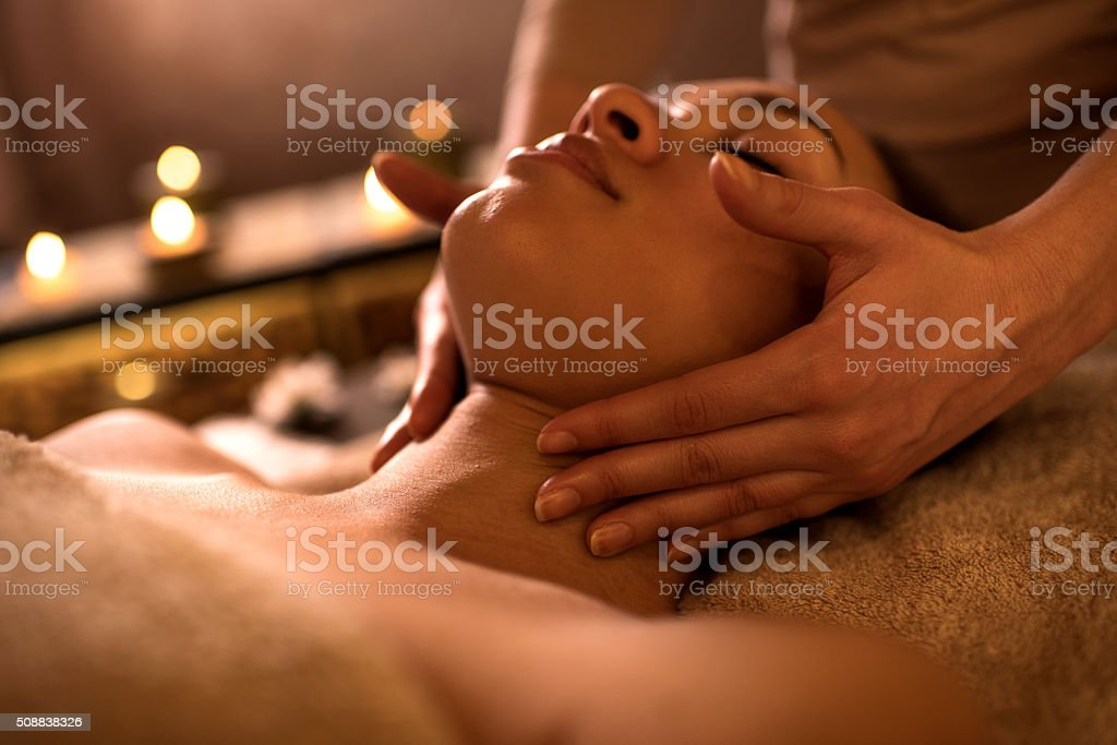 Close-up of African American woman receiving facial massage. stock photo