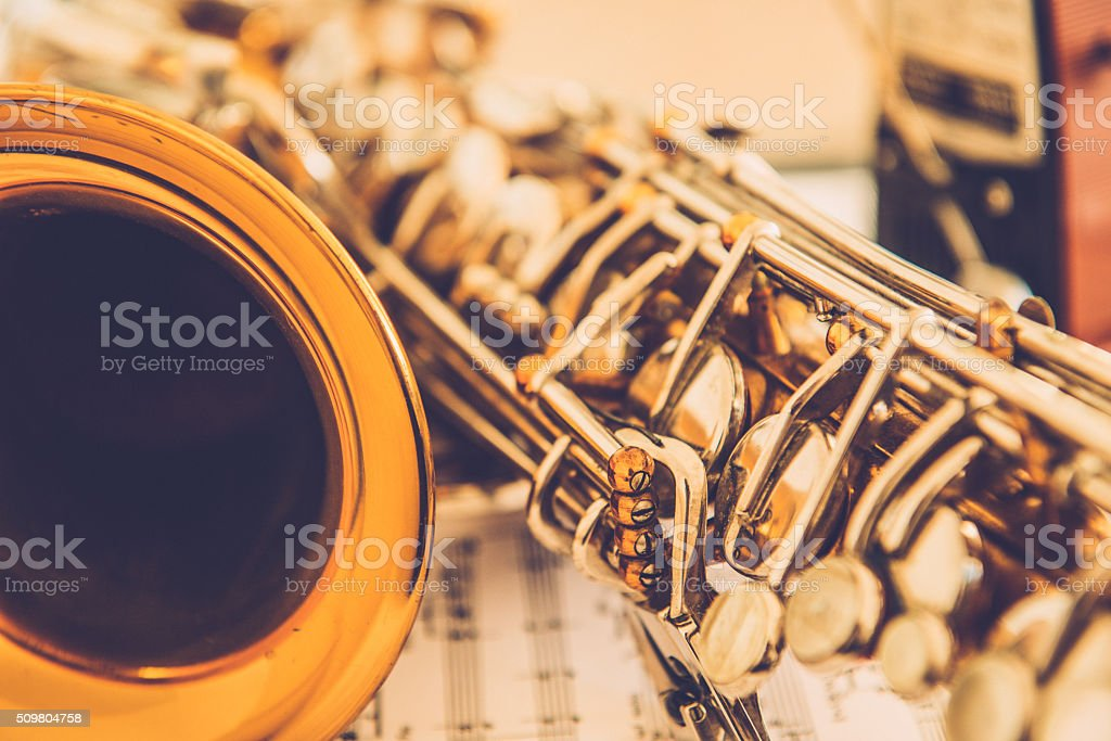 Close-up of Alto Saxophone on Music Sheet and Mechanical Metronome stock photo