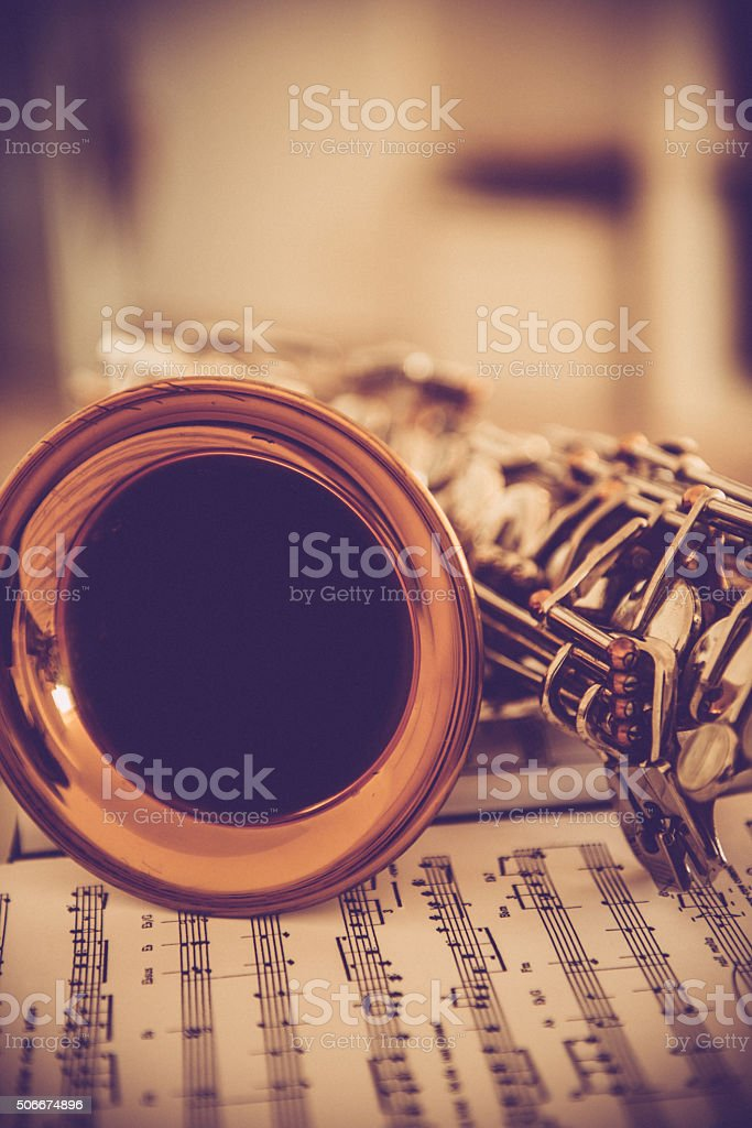 Close-up of Alto Saxophone on Music Sheet, Brown Tones stock photo