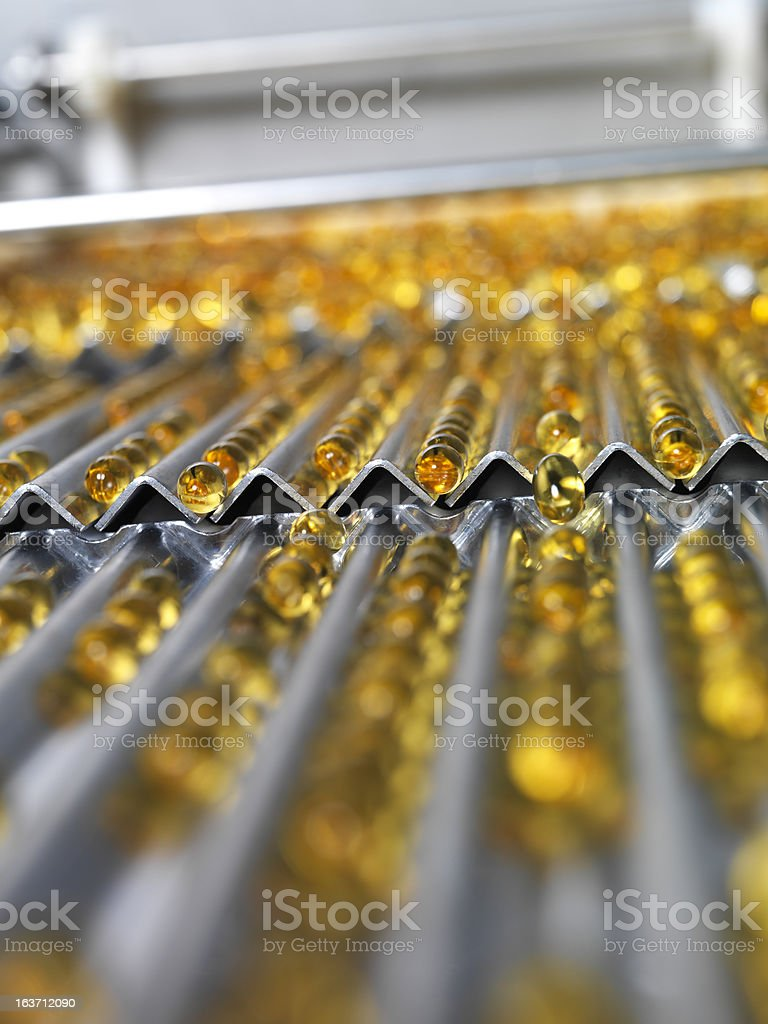 Close-up of amber-colored gel pills at pharmaceutical plant stock photo