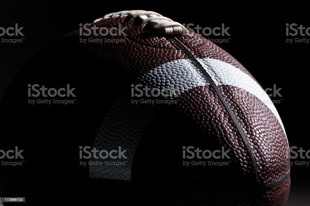 Close-up of American football with dramatic lighting royalty-free stock photo