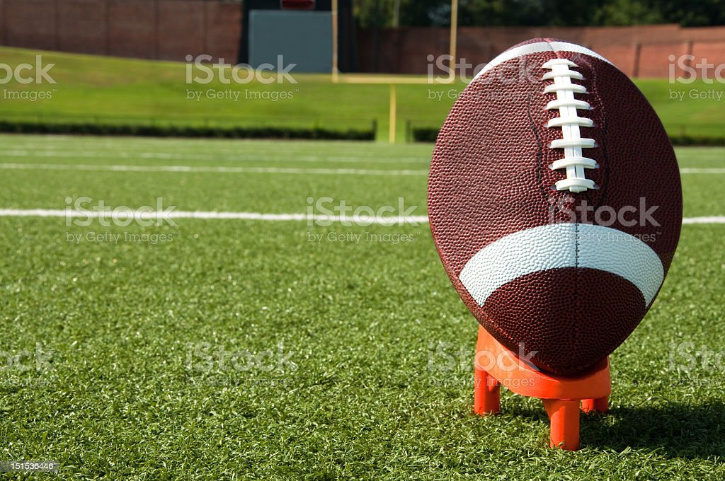 Close-up of an American football on a tee on turf stock photo