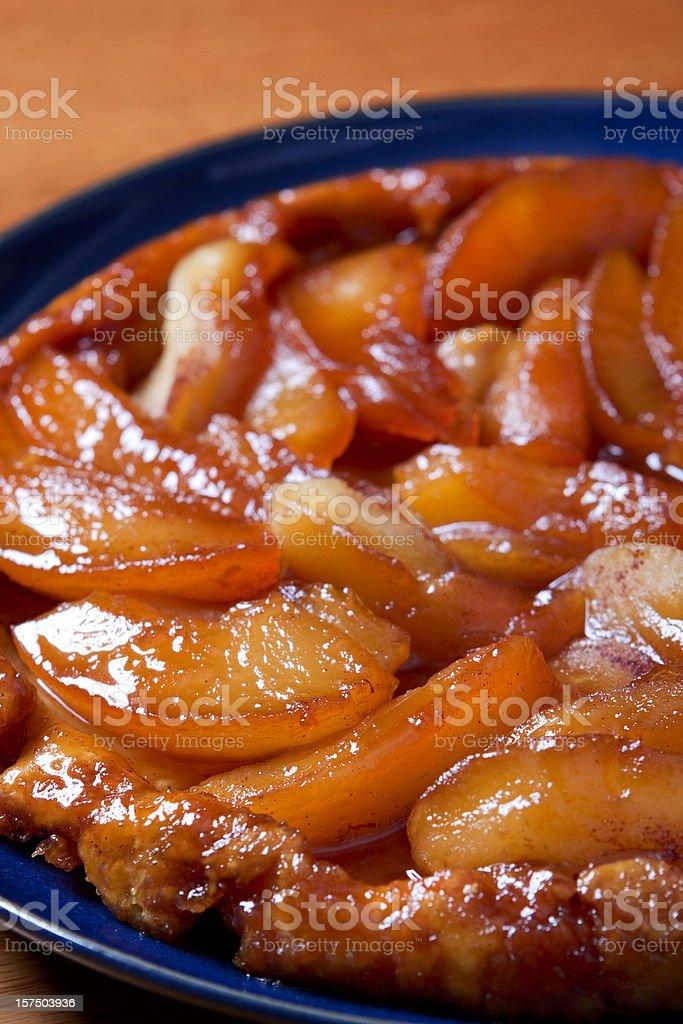 Close-up of an apple tarte tatin in a blue bowl stock photo