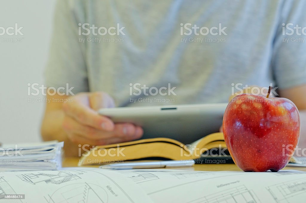 Close-up of an apple with man working on some blueprints stock photo