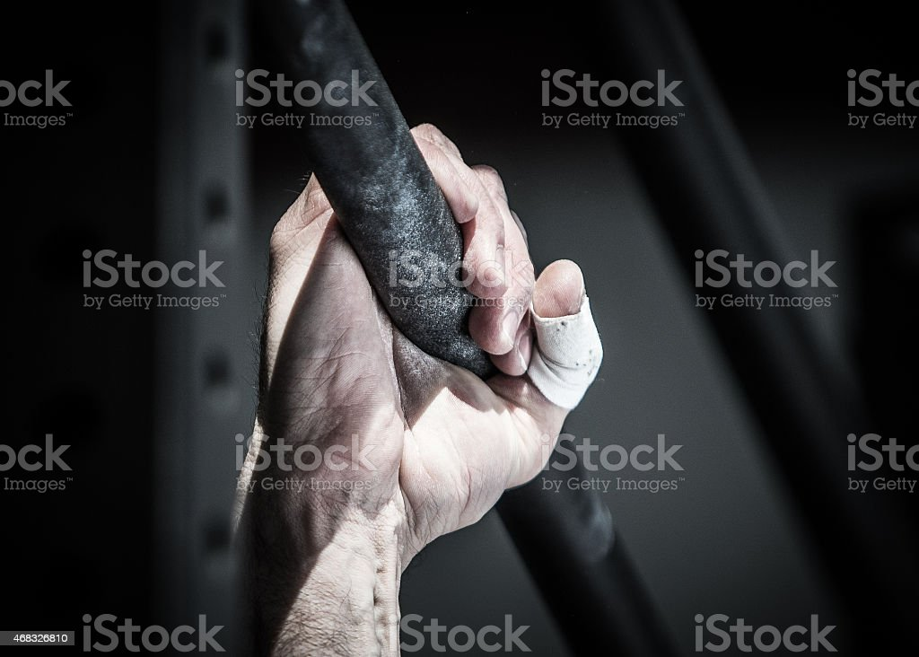 Close-up of an athlete hand with chalk gripping an iron bar stock photo