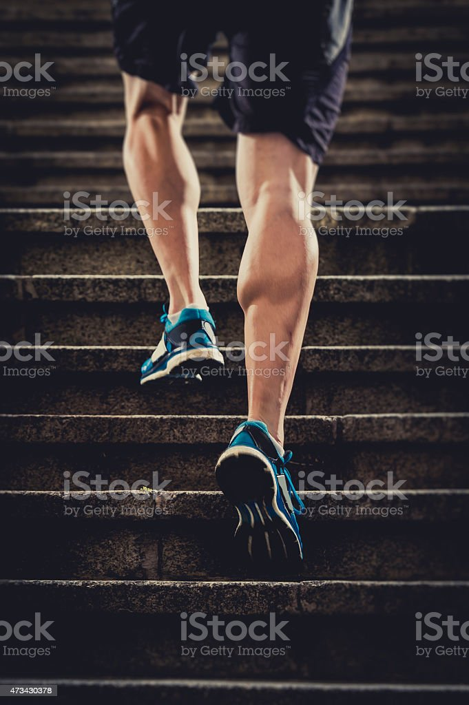 Closeup of an athletic man's legs running up stairs stock photo