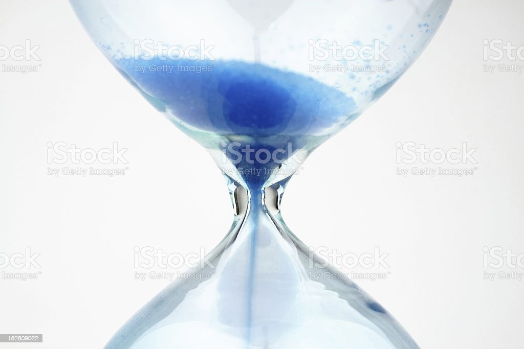 Close-up of an hourglass with blue sand stock photo