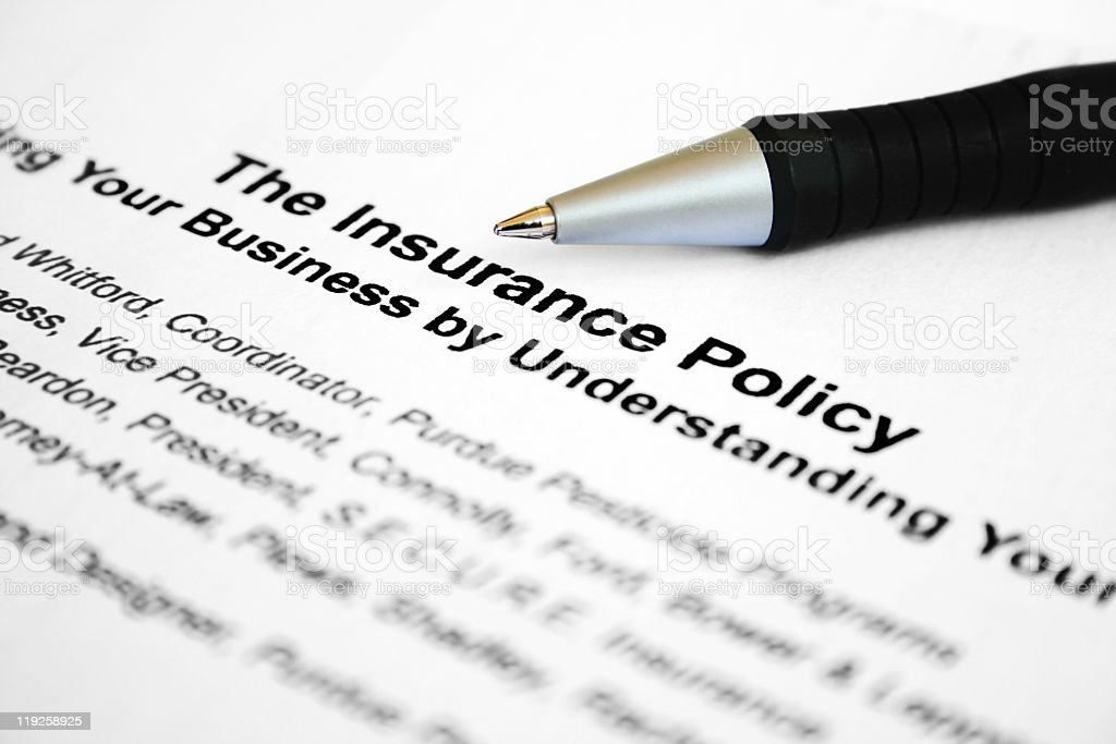 A close-up of an insurance policy with a pen lying on top royalty-free stock photo