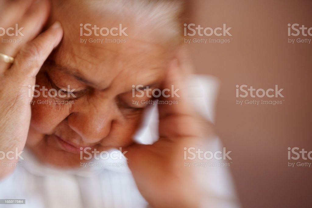 Closeup of an old woman having a severe headache royalty-free stock photo