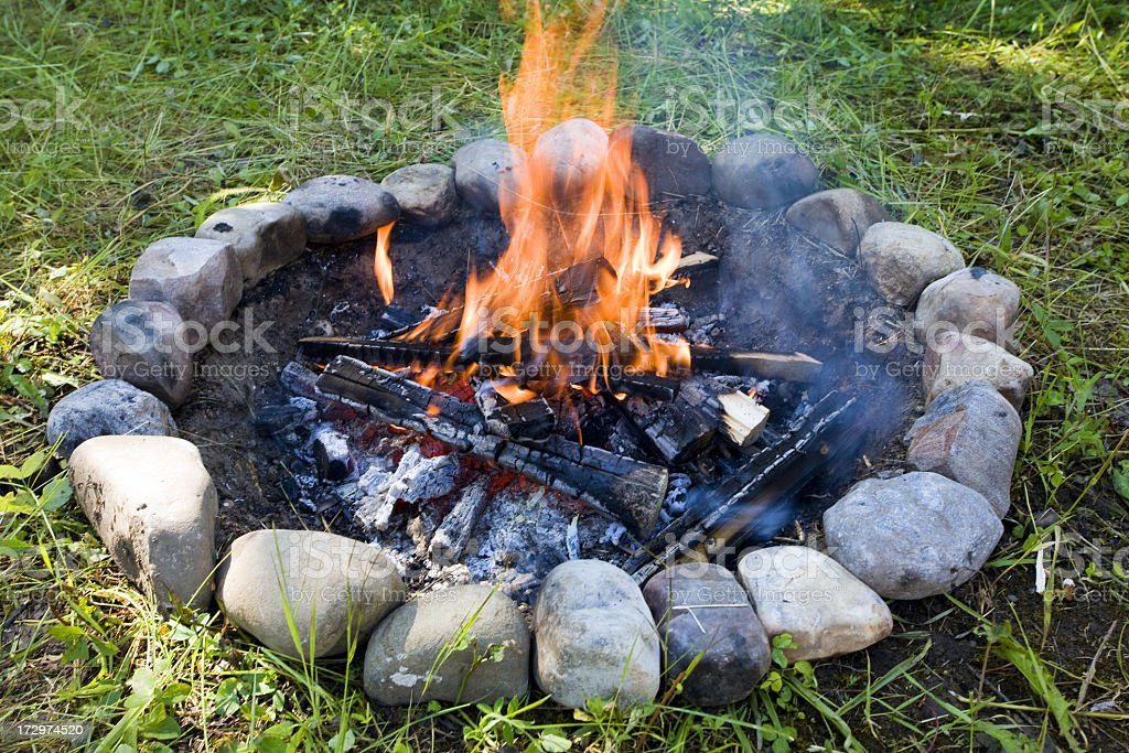 Close-up of an open flame campfire on stone and grass royalty-free stock photo