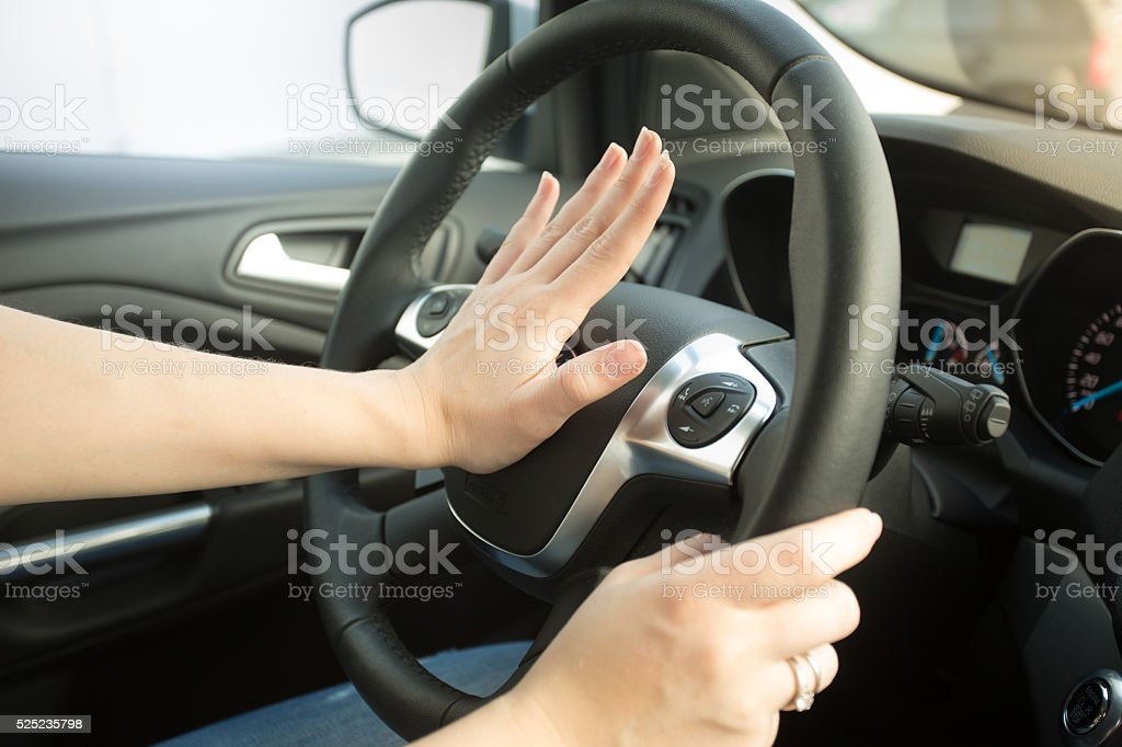 Closeup of annoyed woman driving car and honking stock photo