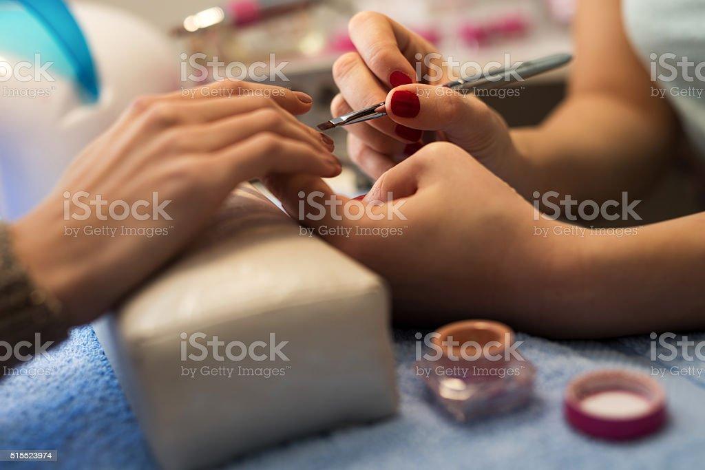 Close-up of applying nail gel on fingernails. stock photo