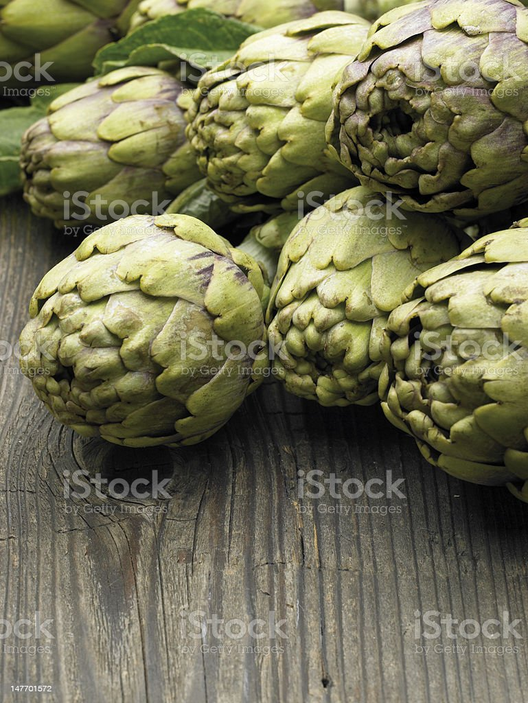 Close-up of artichokes on wooden table stock photo