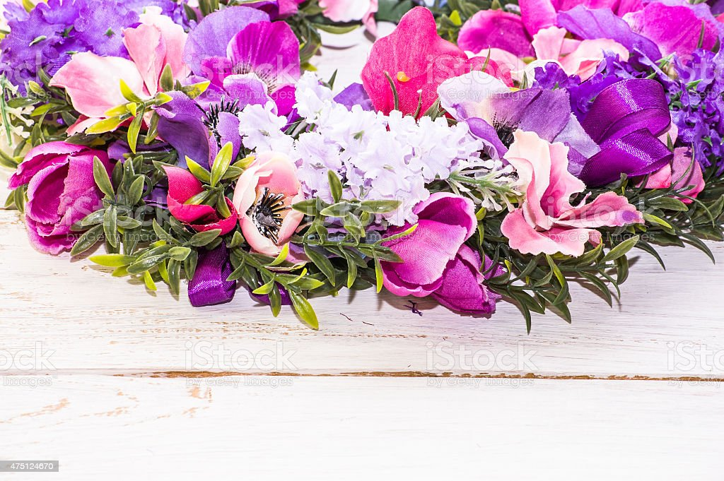Closeup of artificial flower garland isolated on white wood stock photo