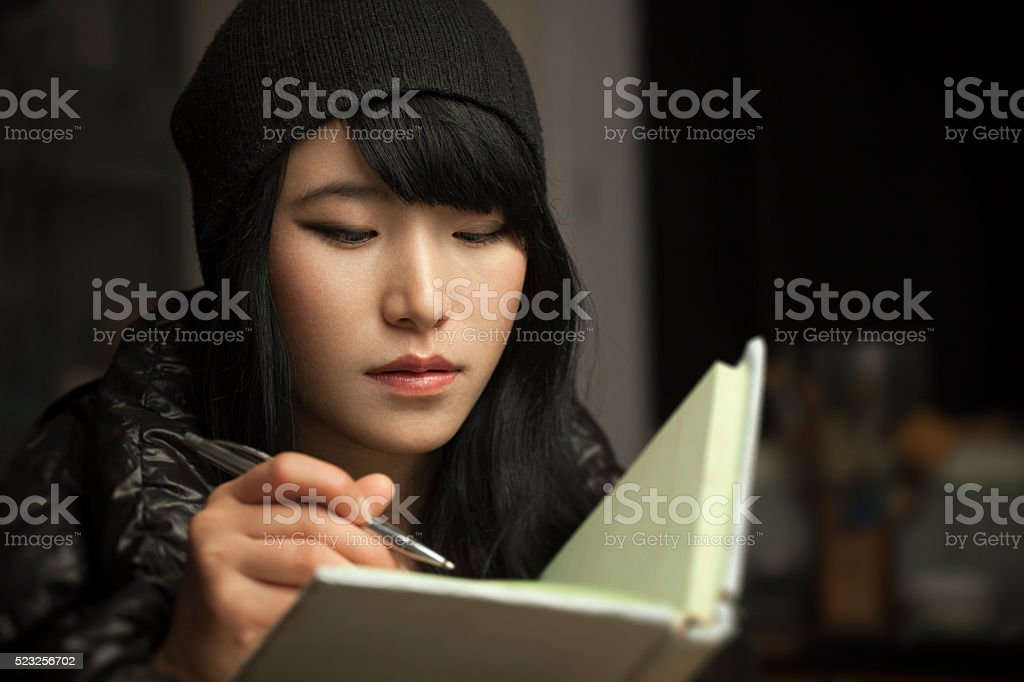 Close-up of Asian girl student writing in a notebook. stock photo