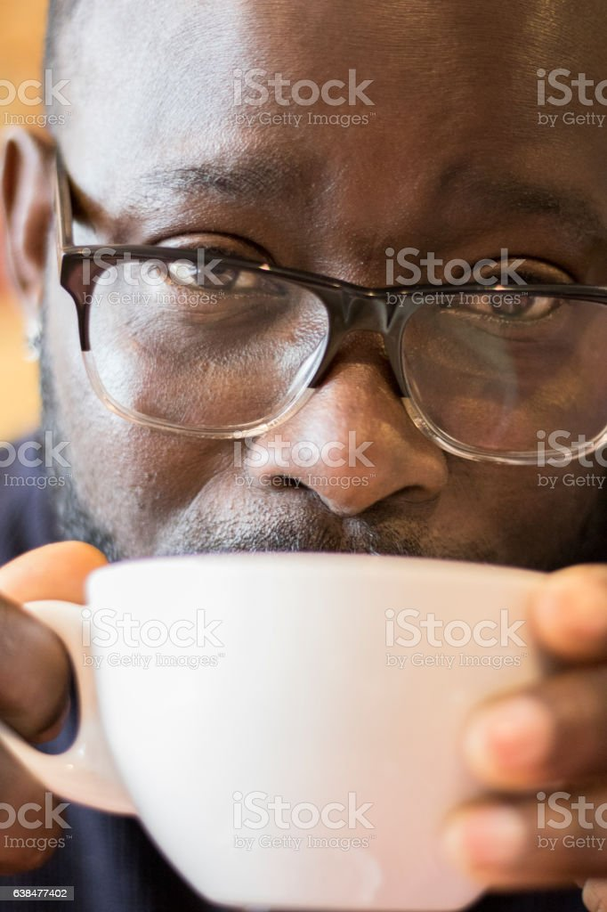Close-up of attractive Afro-Caribbean male supping hot drink stock photo