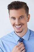 Closeup of Attractive Business Man Adjusting Tie