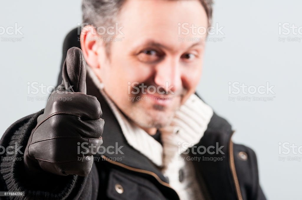 Closeup of attractive man thumb up and smile stock photo