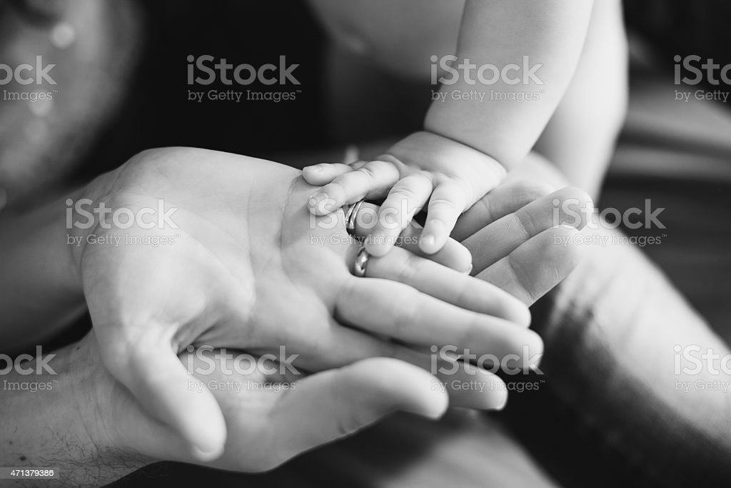 Closeup of baby's and parent's hands. black and white picture stock photo