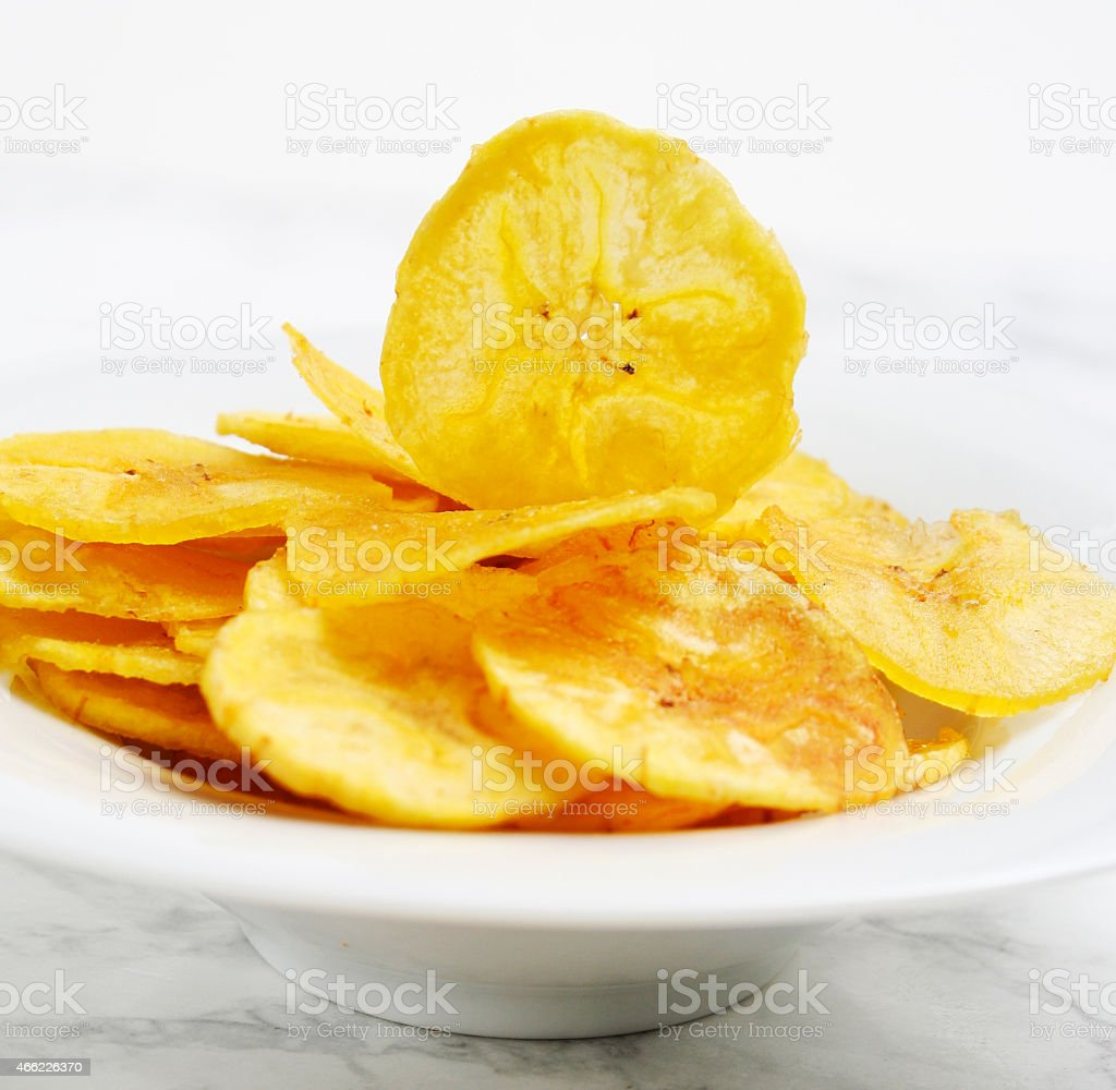 Close-up of banana chips in small bowl stock photo