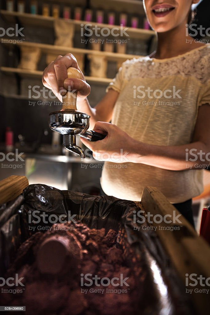 Close-up of barista tamping coffee in a cafe. stock photo