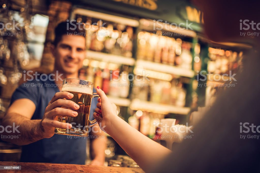 Close-up of bartender giving beer to a customer in bar. stock photo