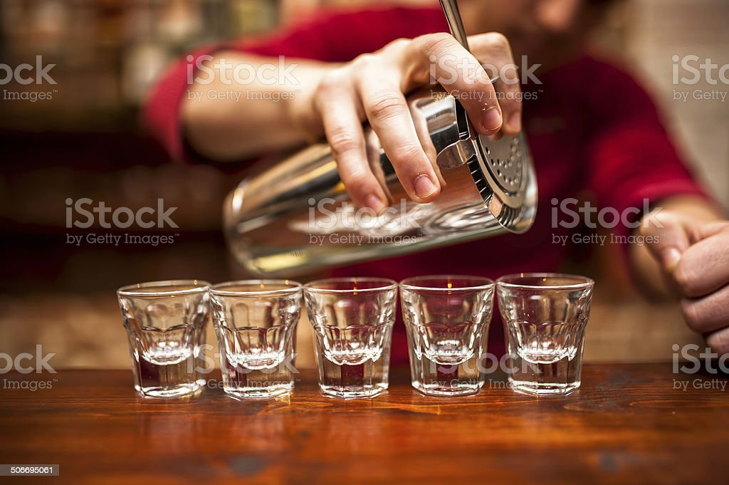 Close-up of bartender hand pouring alcoholic drink in nightclub, stock photo