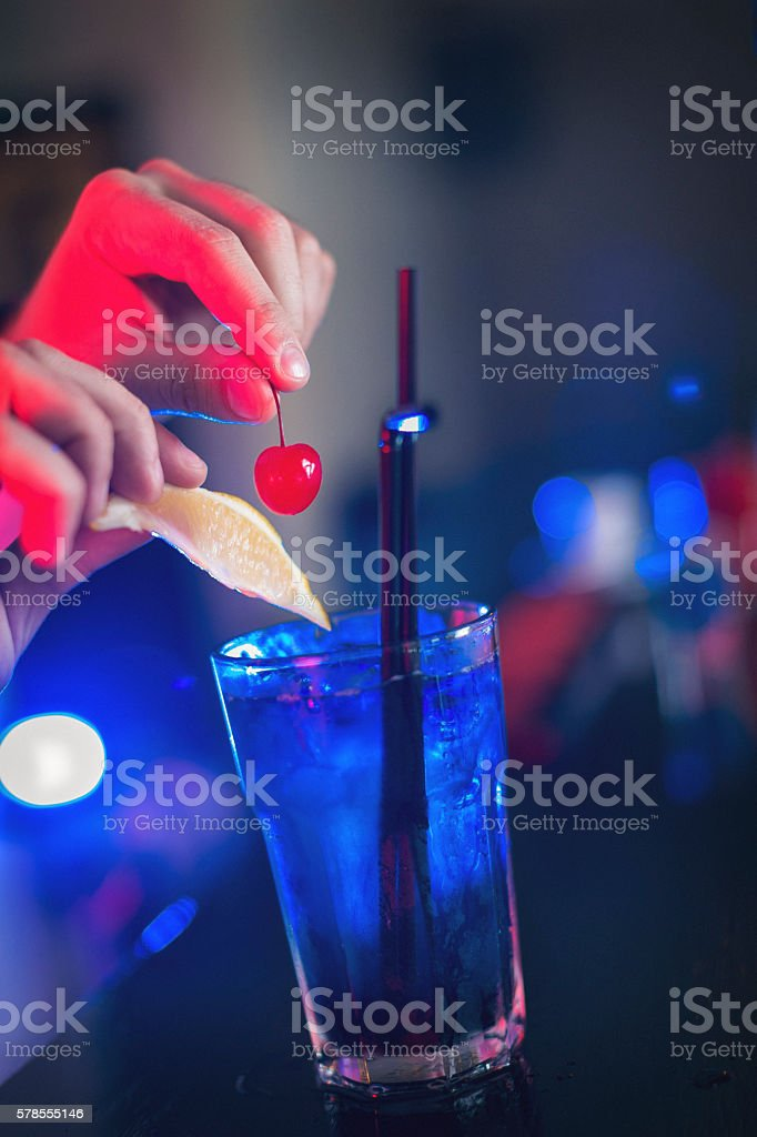 Closeup of bartender hands decorating cocktail stock photo