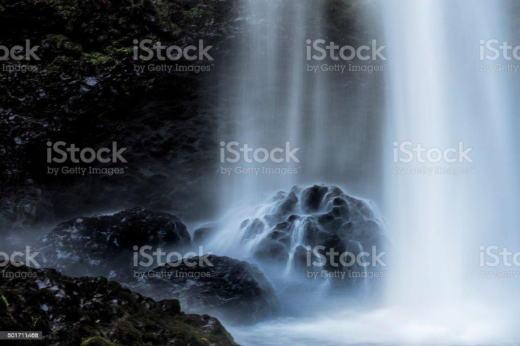 Closeup of base of waterfall hitting boulders stock photo