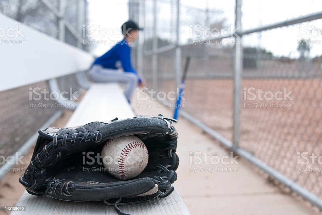 Close-up of baseball ball and glove with boy out of focus stock photo