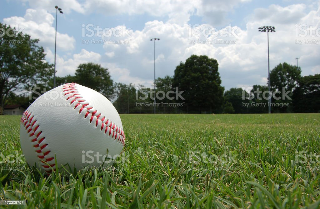 Closeup of baseball sitting in grassy field under cloudy sky stock photo
