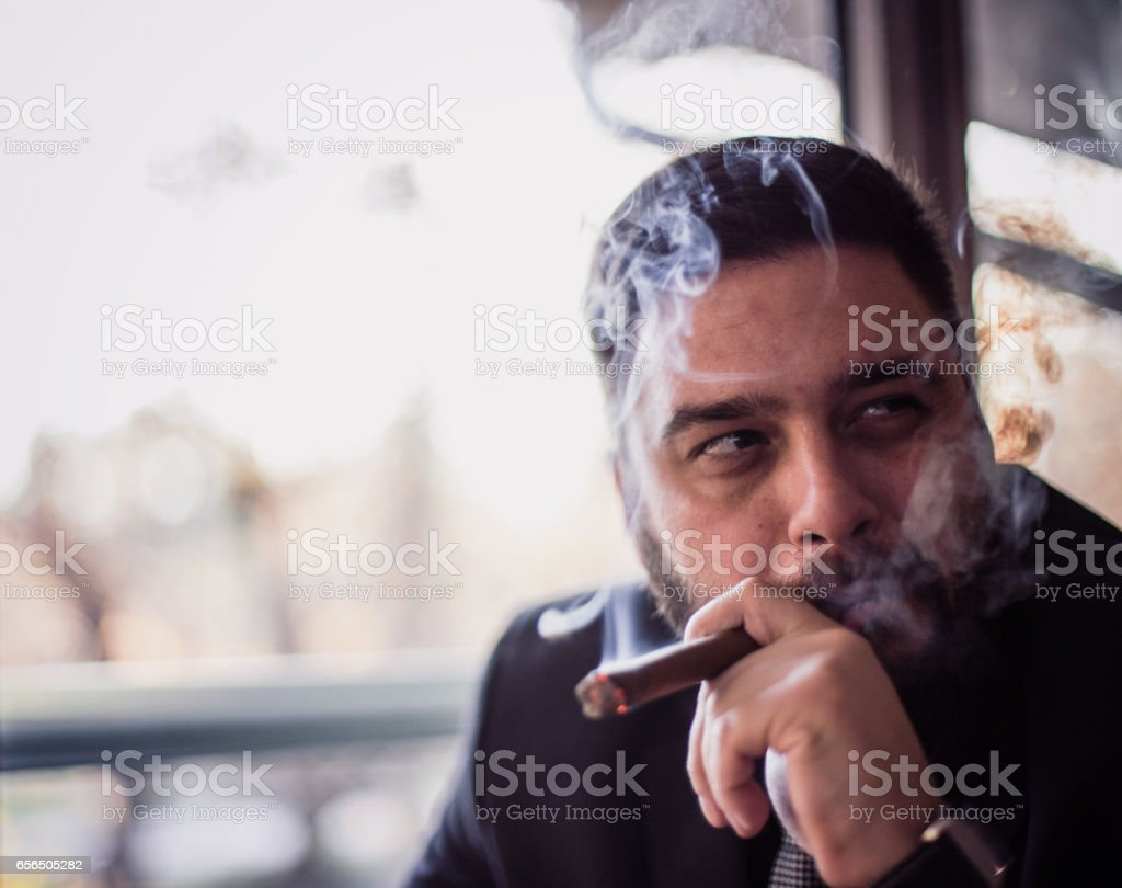 Close-up of bearded caucasian man smoking a cigar stock photo