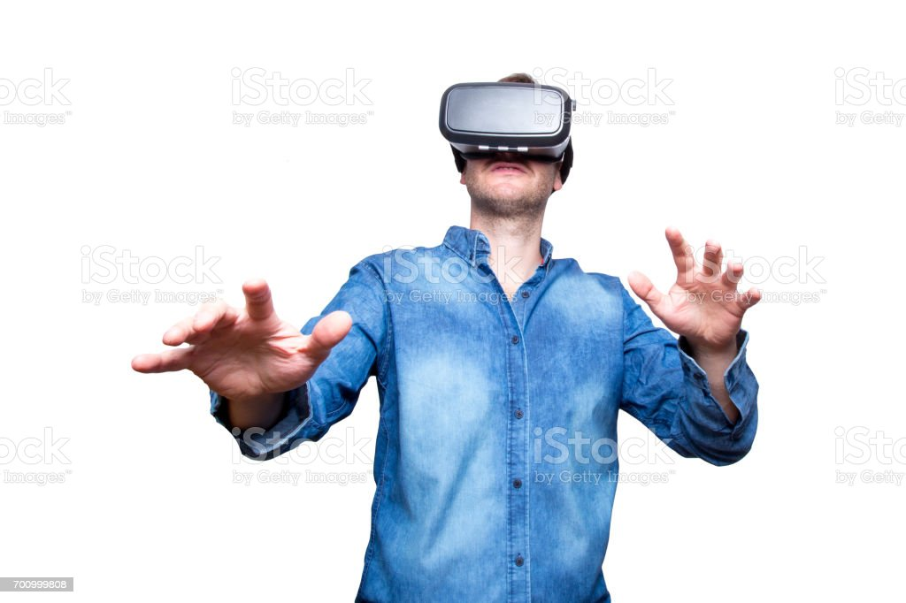 Closeup of bearded young man wearing virtual reality goggles. Smartphone using with VR headset. Horizontal, blurred. White background stock photo