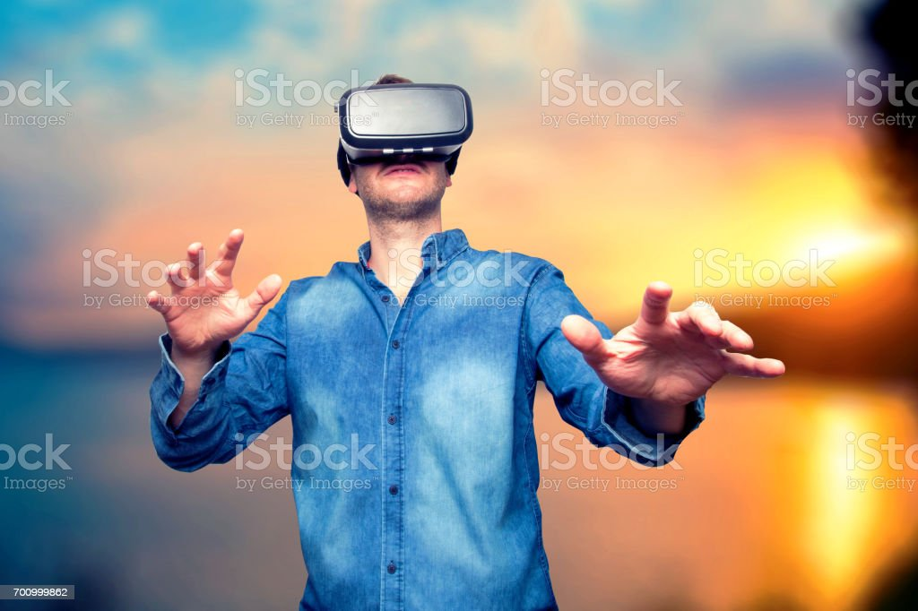 Closeup of bearded young man wearing virtual reality goggles. Smartphone using with VR headset. Horizontal, blurred. Sunset background stock photo