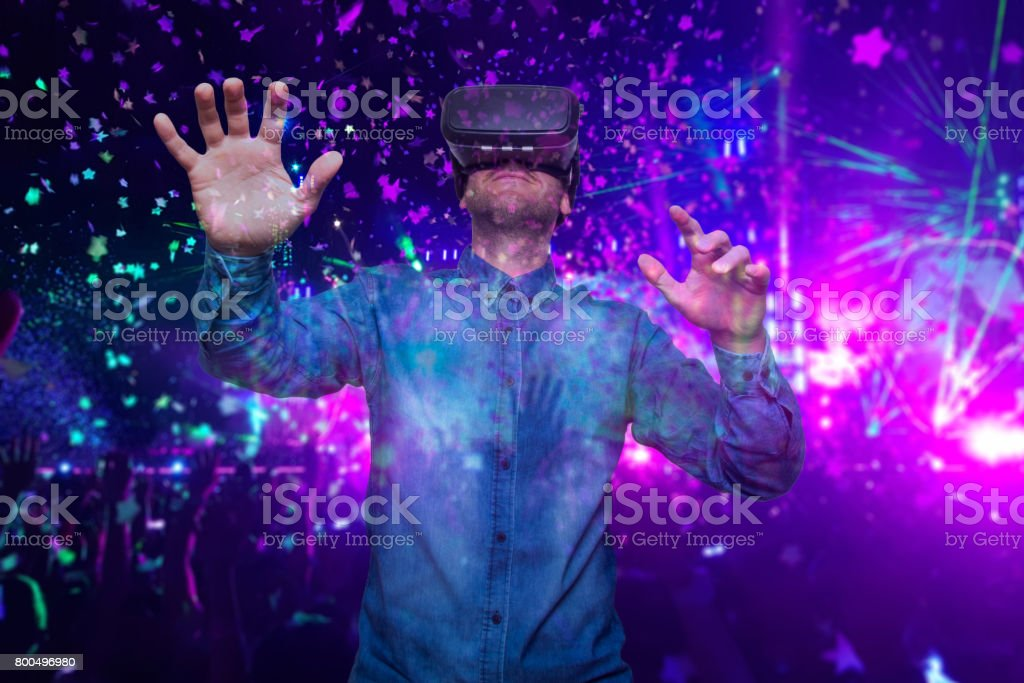 Closeup of bearded young man wearing virtual reality goggles. Smartphone using with VR headset. Horizontal, blurred. Concert background stock photo