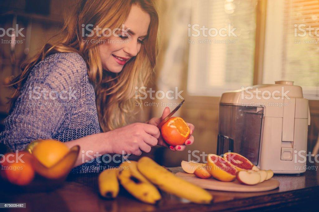 Close-up of beautiful girl peeling orange and grapefruit to make smoothie stock photo