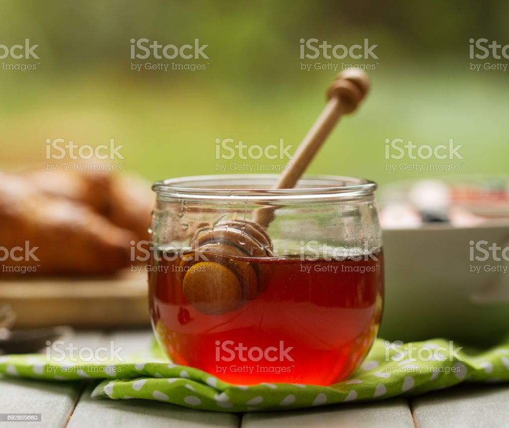 Closeup of beautiful honey in jar with honey spoon on table with kitchen towel. Breakfast. Kitchen Background. stock photo