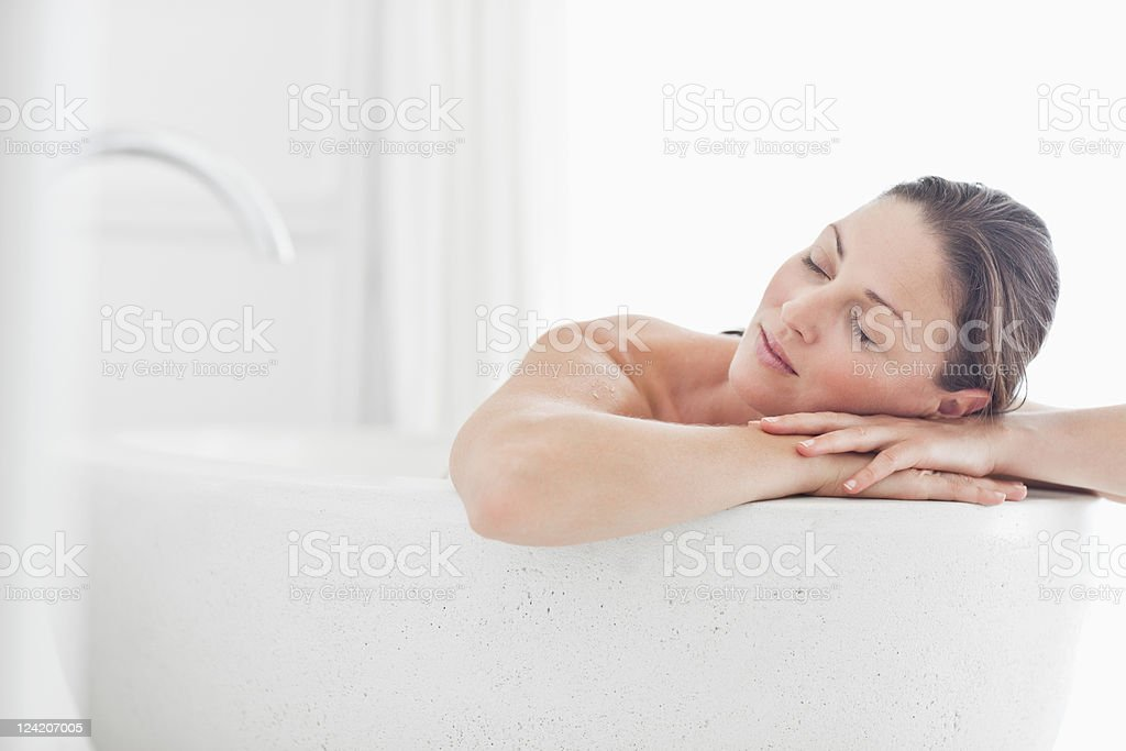 Close-up of beautiful mid adult woman relaxing in bathtub with eyes closed stock photo