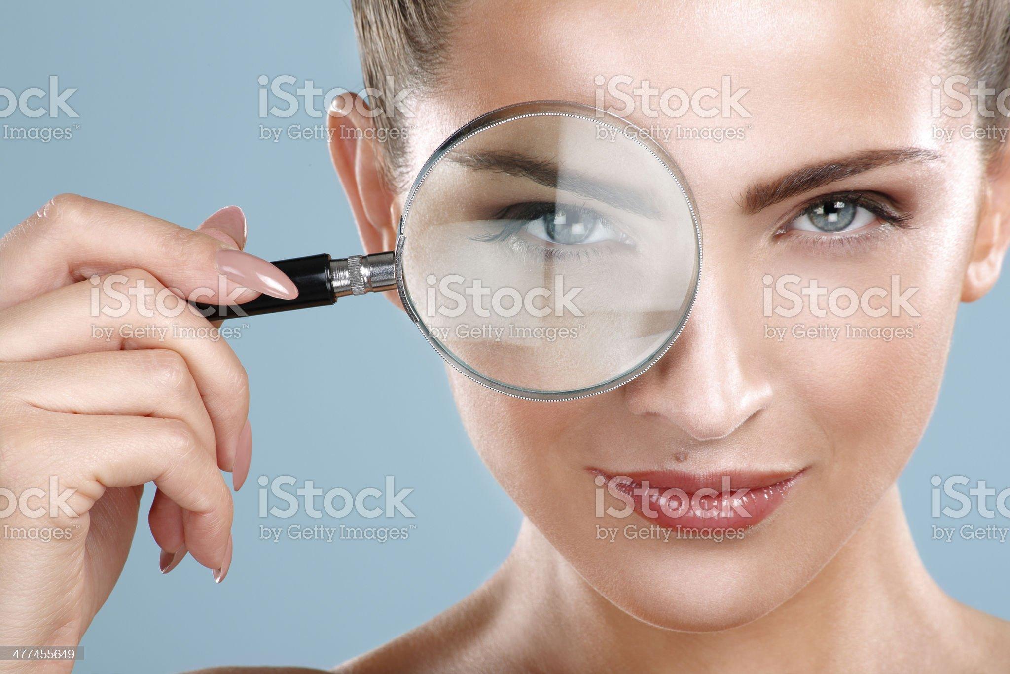 Closeup of beautiful smiling woman looking trough glass royalty-free stock photo