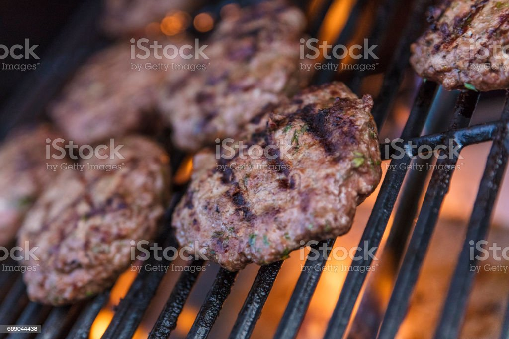 Close-up of beef patties cooking on a charcoal to make hamburgers. stock photo