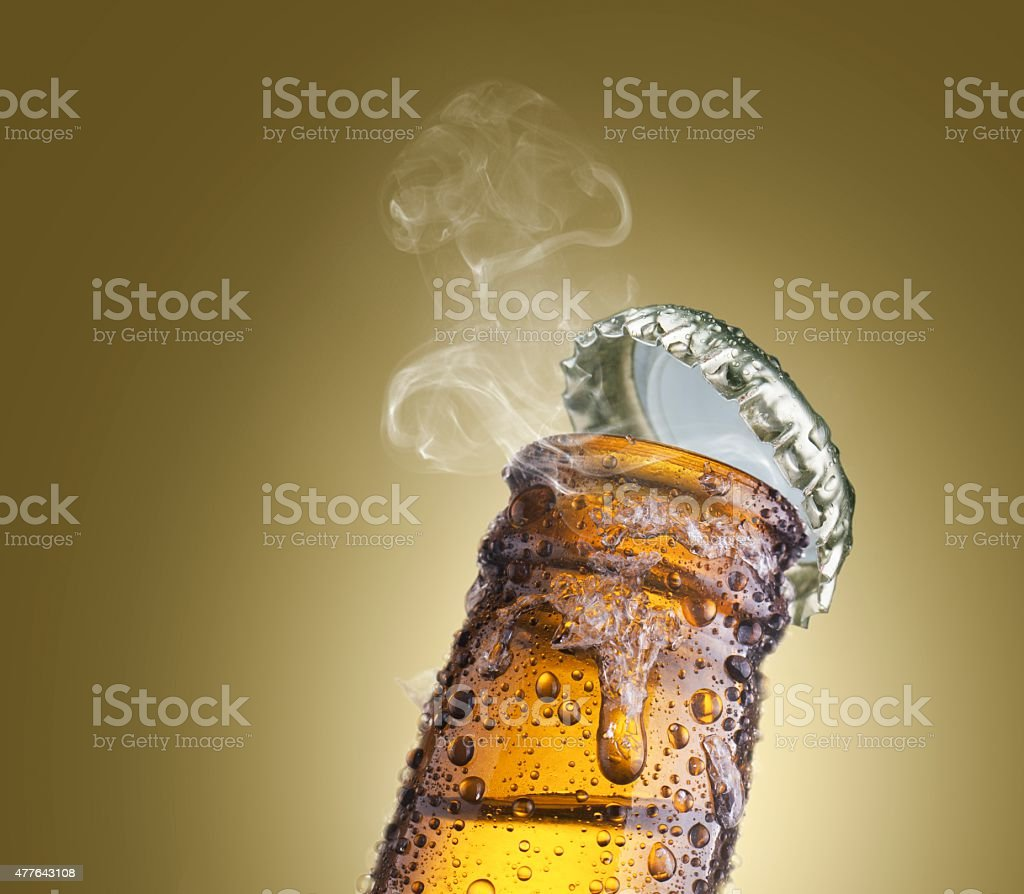close-up of beer bottleneck with droplets, ice, smoke, and cap stock photo