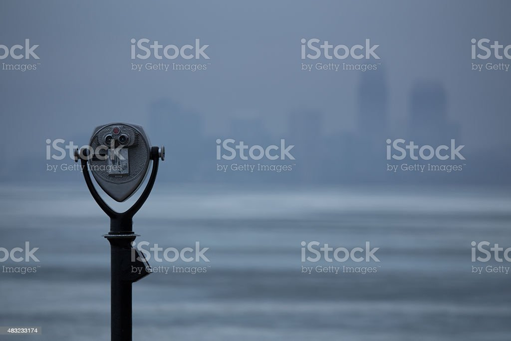 Closeup of binoculars pointed toward a fogged in city. stock photo