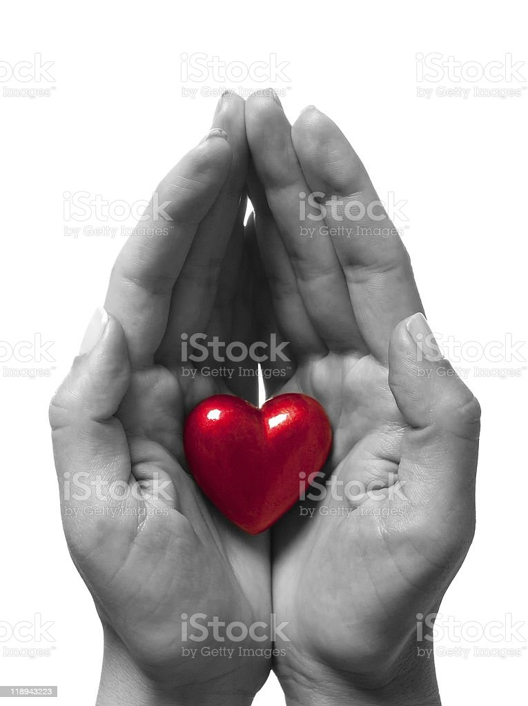 Close-up of black and white hands holding red heart royalty-free stock photo