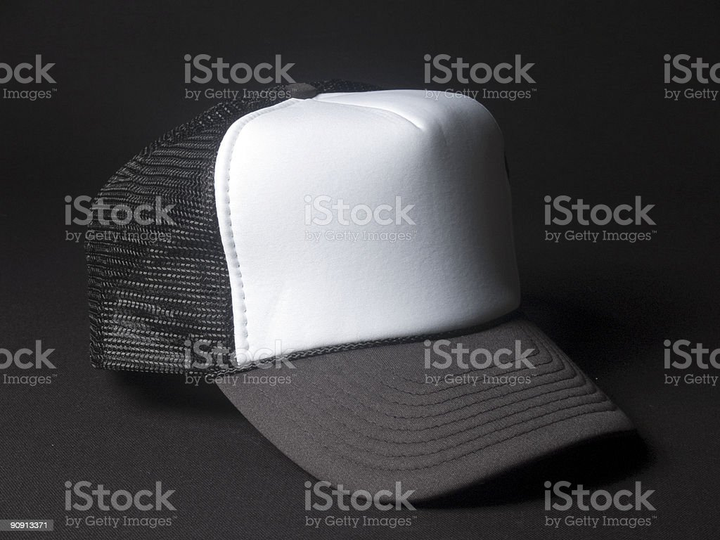 Close-up of black and white trucker hat on black background royalty-free stock photo