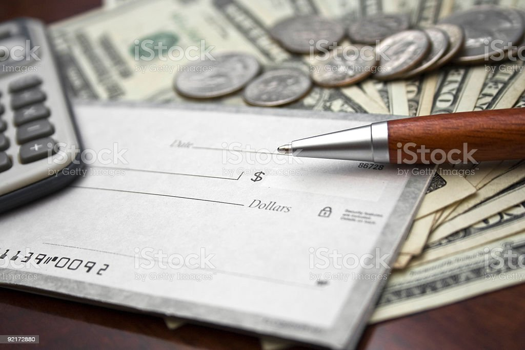 Close-up of blank check, US bills/coins, calculator and pen stock photo