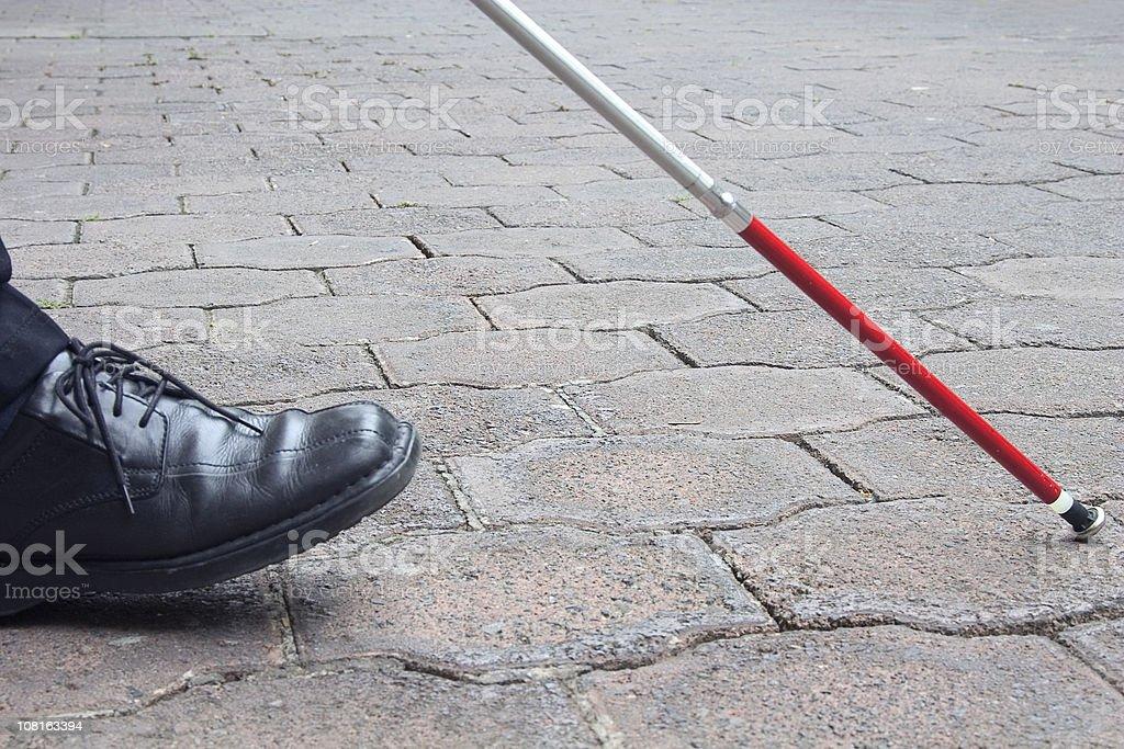 Close-Up of Blind Man's Black Shoe and White Cane Walking stock photo