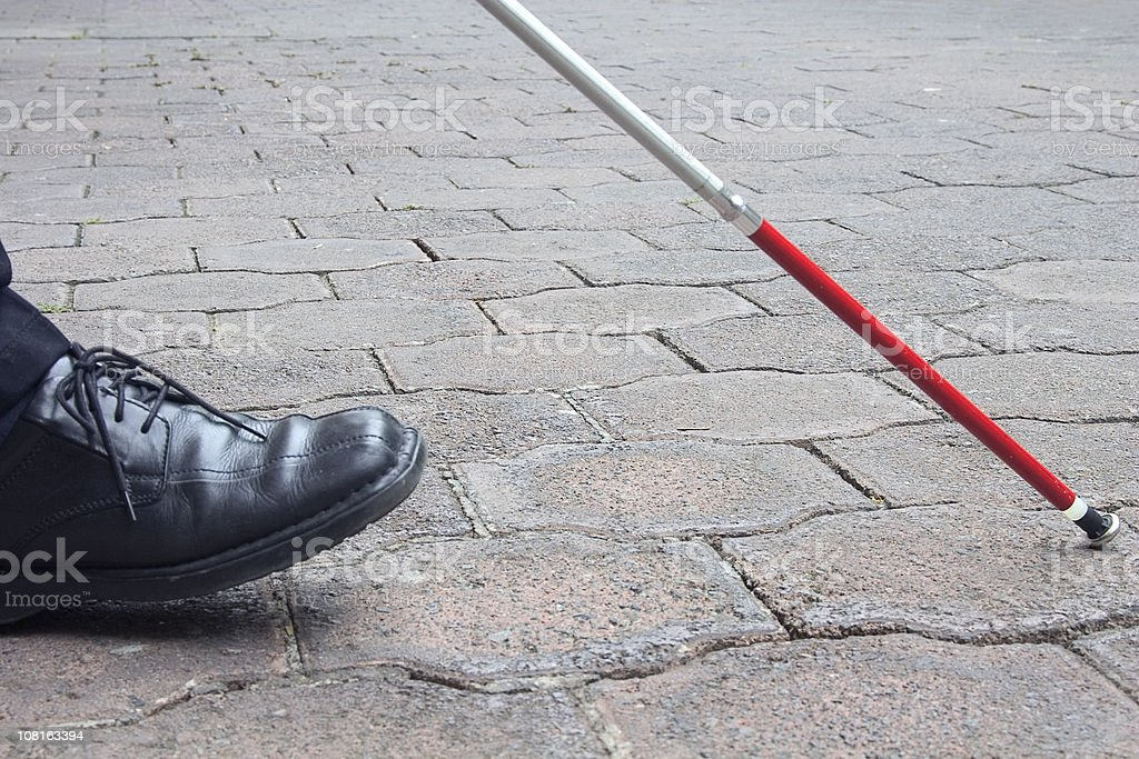 Close-Up of Blind Man's Black Shoe and White Cane Walking stock photo